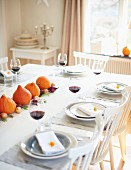 A table laid for Thanksgiving decorated with pumpkins and onions with glasses of red wine at each place