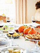 A table laid for Thanksgiving with turkey, side dishes, pecan pie and red wine