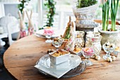 A wooden table decorated for Easter with mini rolls, a rabbit figure, plants and quail's eggs