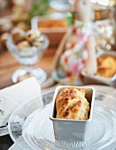 A mini loaf of cheese and thyme bread in a baking tin on a table laid for Easter
