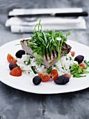 Grilled tuna steak on a bed of rice with tomatoes and olives