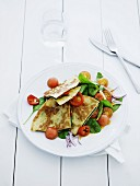 Pancakes filled with baby spinach and tomatoes