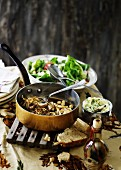 A mushroom medley with bean sprouts and chickpeas in a copper saucepan with a green salad in the background