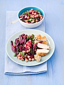 Warm beetroot salad with chickpeas, onions, beetroot leaves and grilled chicken breast
