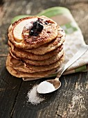 A stack of blueberry pancakes with sugar and blueberries