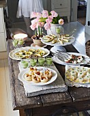 A festive buffet with various canapés on a rustic wooden table