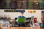 A young man in a cafe holding fresh wheatgrass