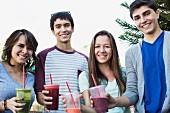 Four young people drinking smoothies
