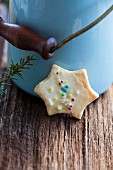 A star-shaped butter biscuit decorated with coloured sprinkles in front of a milk churn