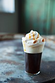 Coffee with whipped cream and caramel sauce on a metal surface