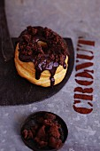 A croissant-doughnut with chocolate glaze and cookies
