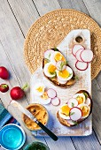 Slices of bread topped with chilli butter, radishes and duck egg