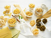 Various sorts of pasta, some in jars and some on a wooden surface