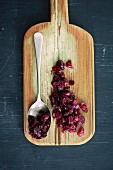 Cranberry jam on a spoon and on a chopping board