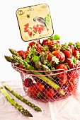 Strawberries and green asparagus in a wire basket with an old-fashioned sign
