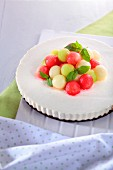 A cream cheesecake decorated with colourful melon balls and peppermint leaves