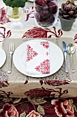 A place setting with a red and white fabric napkin
