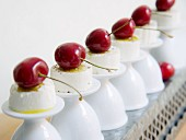 Goat's cream cheese with cherries on upturned egg cups