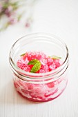 A jar of pomegranate sorbet with mint