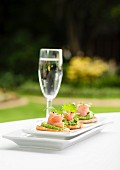 Salmon crostini with a glass of champagne