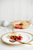 A slice of plum pie on a plate with the rest in a background in a glass dish