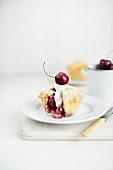 A sliced mini cherry pie with cream