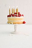 A birthday cream cake with raspberries and golden candles