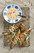 Grilled grey mullet with a sesame seed coating served with peanut sauce