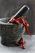 Dried chilli peppers in a mortar
