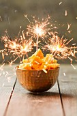 Honeycomb in a copper bowl decorated with sparklers, England