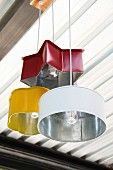 Old baking tins in different colours and shapes as pendent lamps