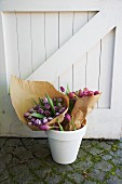 Bunches of pink and purple tulips wrapped in paper in a white flowerpot in front of a white wooden gate