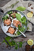 Wholemeal bread topped with butter, smoked salmon and sesame seeds