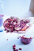 Hands holding a halved pomegranate