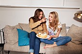 Two young women sitting on a sofa, one feeding the other cake