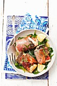 Trout roulade with prosciutto and sage on a bed of fried spinach
