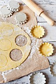 Shortcrust pastry on a work surface and in metal tins with a rolling pin