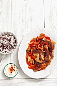 Roast chicken legs with peppers and onions served with a side of rice