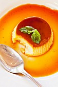 Creme caramel garnished with mint leaves with a bite taken out