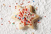 A star biscuit with colourful sprinkles in icing sugar