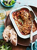Aubergine and mozzarella bake with slices of bread