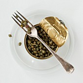 A tin of capers with a fork