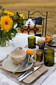 Place setting with wooden bowl, horn beaker and posy with guinea fowl feather