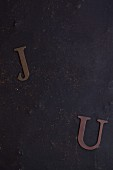Paper J and U letter on a dark background