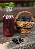 A blackberry smoothie and fresh blackberries on a wooden surface