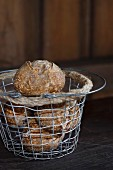 Homemade wholemeal rolls in a wire basket