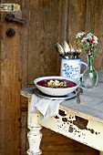 Beetroot soup with sheep's cheese gremolata on a rustic table