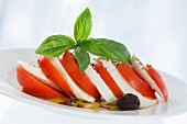Layers of tomato and mozzarella, basil and olives