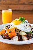 A fried egg on a bed of fried potatoes mushrooms turnips served with orange juice (USA)