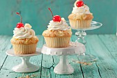 Pina colada muffins with cream and glace cherries